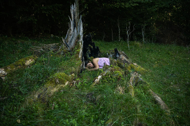 femeie întinsă într-un trunchi de arbore