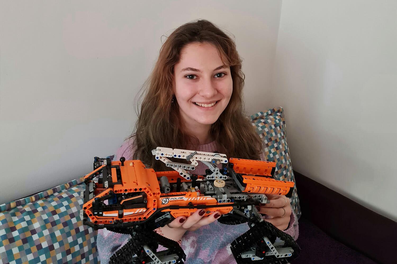 Aici apare o fată zâmbind, ținând în mână o autospecială construită din piese de Lego Technic.