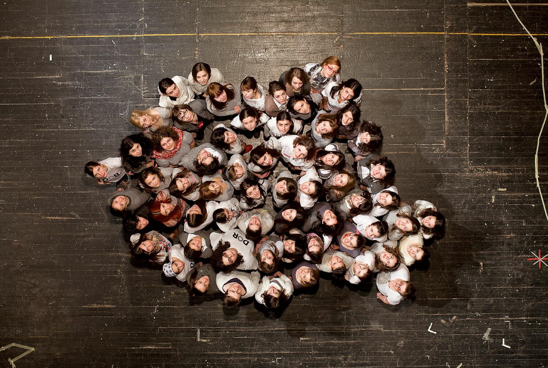 Poza ar putea arăta mai multe femei așezate pe o scenă, în forma hărții României, privind în sus, fotografiate de sus.