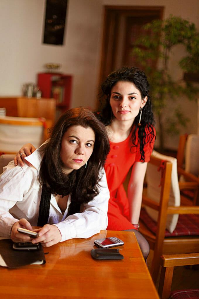 Poza poate arăta două femei stând la o masă, una aproape de cealaltă. Una ține un telefon în mână și privește deasupra camerei, cealaltă stă în spatele ei, o atinge pe umăr și privește direct în cameră.