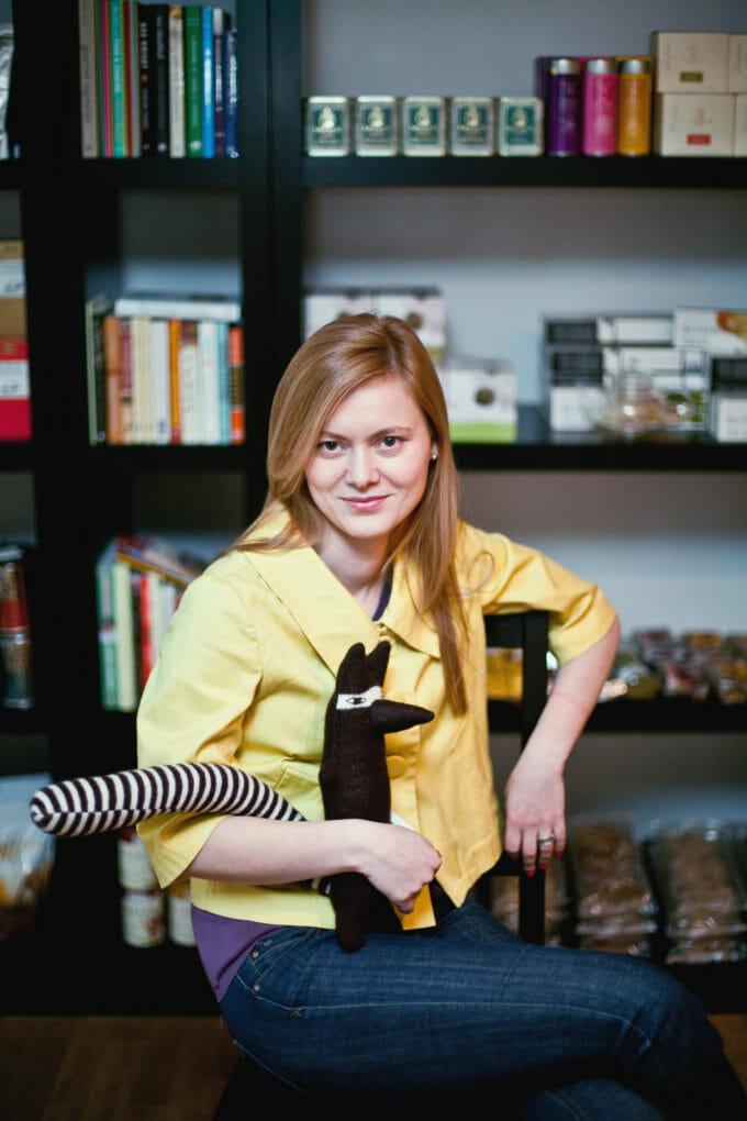 Poza poate arăta o femeie ținând în mână un animal mic din pluș. Femeia stă pe un scaun și privește zâmbind spre cameră.