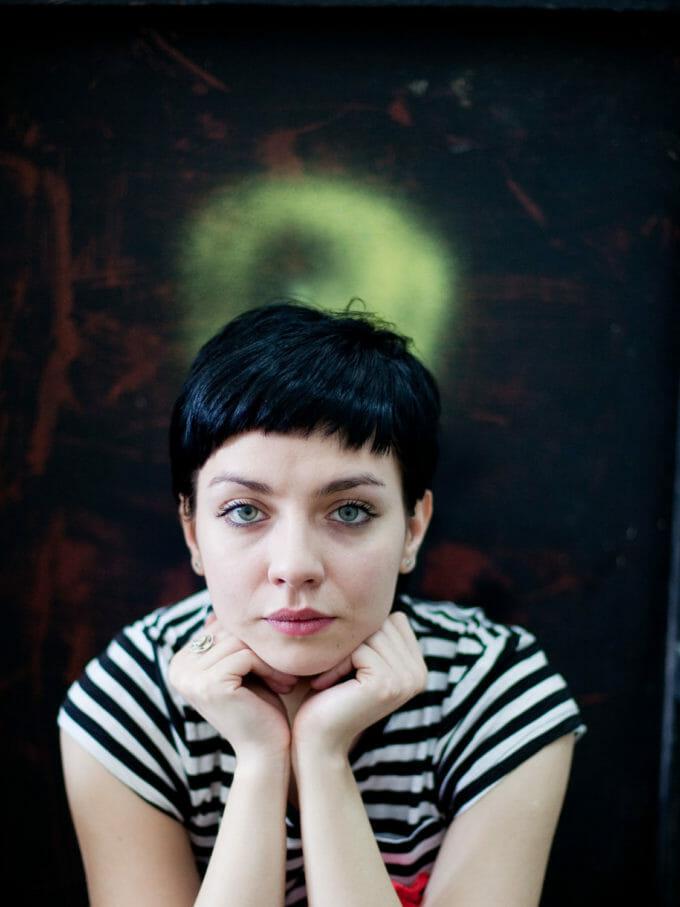 Poza poate arăta o femeie cu părul scurt și ochii albaștri, care își sprijină bărbia între mâinile împreunate și privește în cameră.
