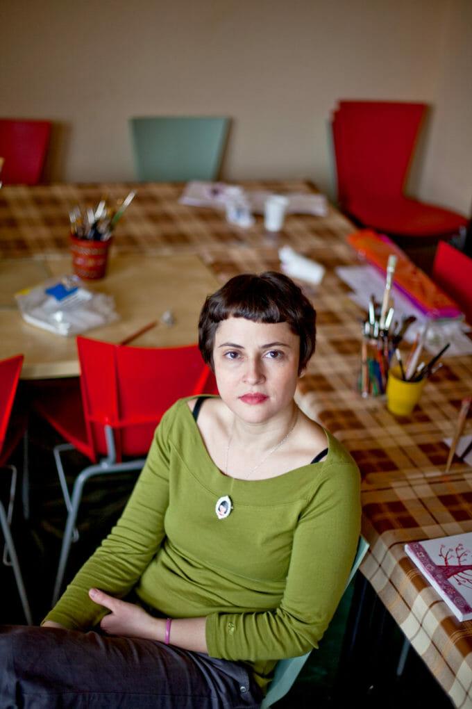 Poza arată o femeie așezată pe un scaun, lângă o masă cu caiete, creioane și pensule. Femeia e calmă și privește în cameră, care o fotografiază de sus.