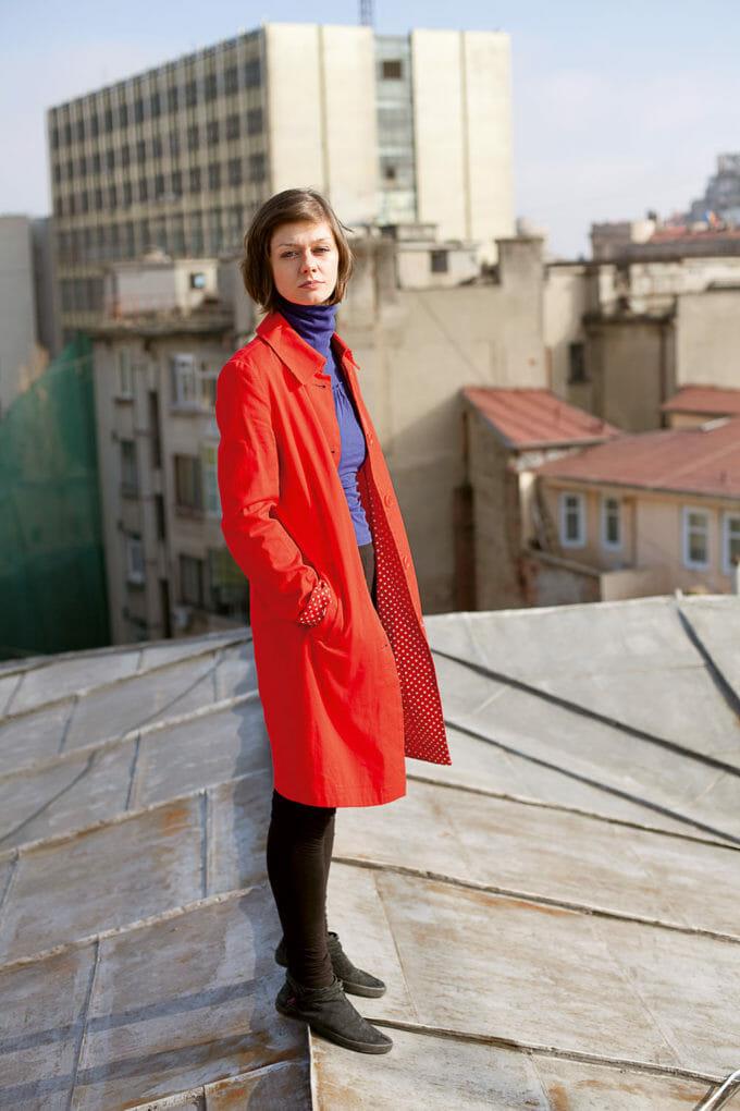 Poza arată o femeie stând în picioare pe un acoperiș, în timpul zilei, privind hotărât înspre cameră, care o fotografiază din lateral.