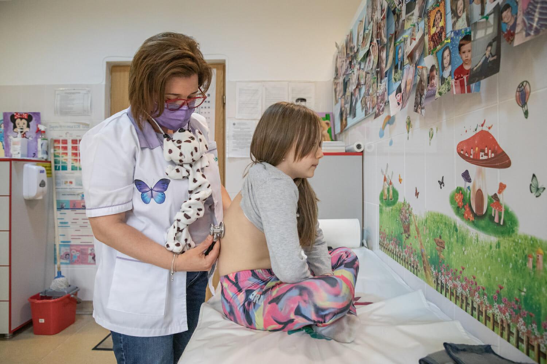 Doctor Butum consultă o fetiță, lângă un perete decorat cu fotografii ale copiilor pe care îi îngrijește.