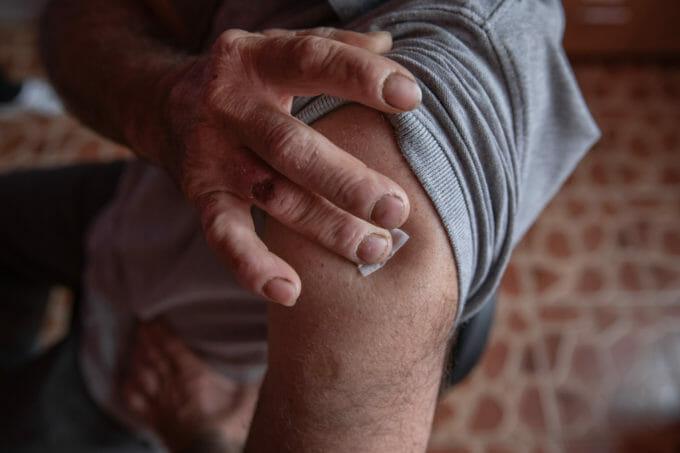 Un pacient ține un bandaj la locul vaccinării