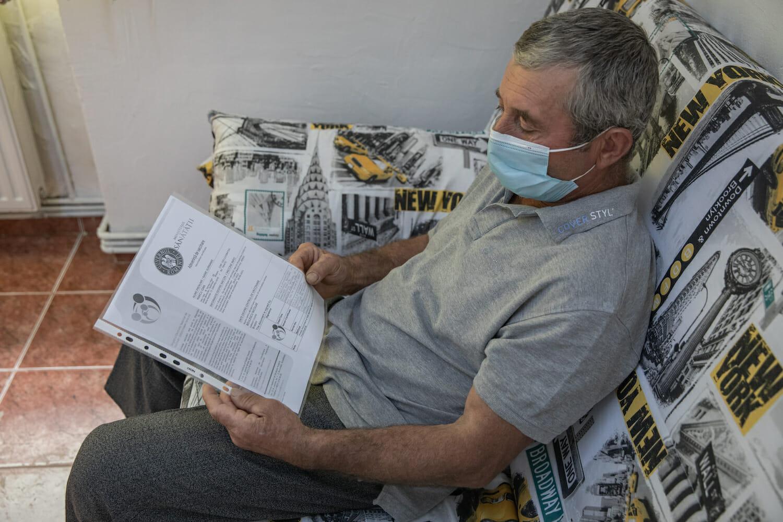Un pacient așteaptă pe canapea cu adeverința de vaccinare în mână.