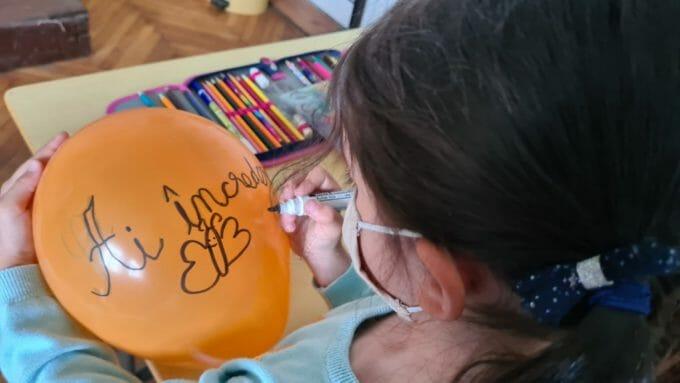 O elevă desenează pe un balon