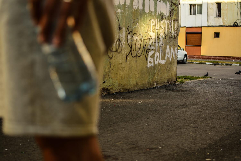 """În cartierul de blocuri, pe un colț de bloc scrie """"Puștiu zis golan""""."""