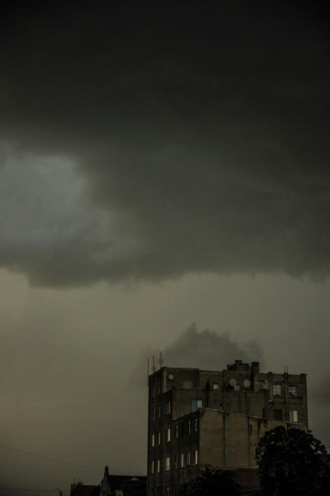 Un bloc gri pe un fundal de cer înnorat.