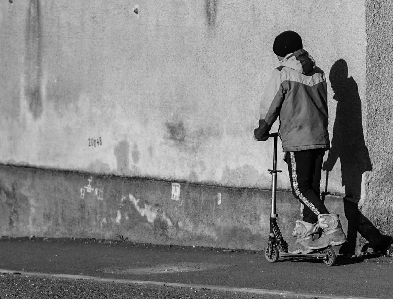 Un copil pe o trotinetă lângă un bloc