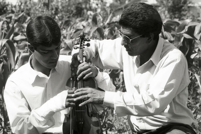 Caliu îl învață pe Robert să cânte la vioară (fotografie de arhivă).