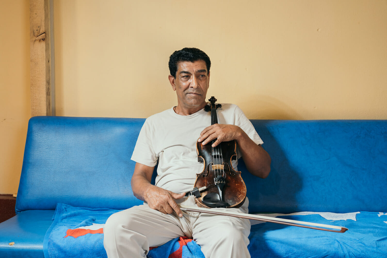 Caliu acasă la Clejani, cu vioara în mână pe canapea