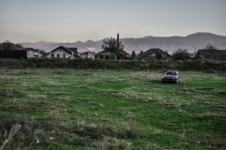 Marginea de sus a orașului - un șir de case și o mașină oprită pe un câmp.